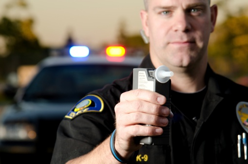 a police officer holding up a breathalyzer