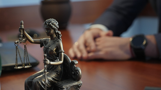 Statue of justice on the table against the background of the hand gestures of a man, a lawyer or a judge