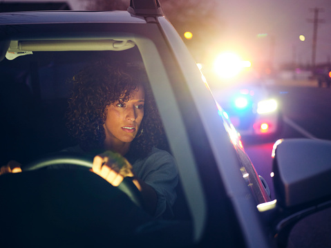 A young woman, being stopped by police at night for a traffic violation.